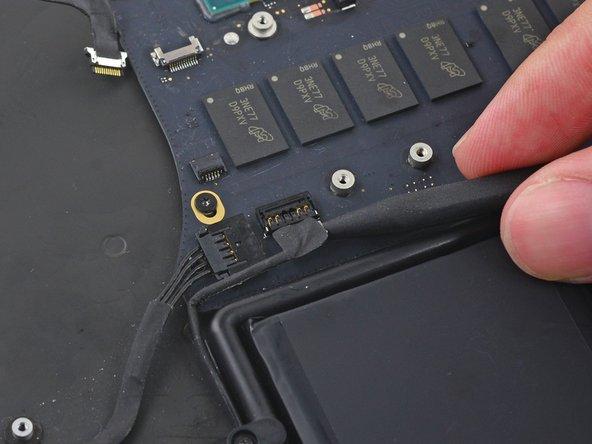 スパッジャーの先端を使って、右側スピーカーのコネクターをロジックボード上のソケットからまっすぐ引き上げます。