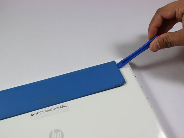 Use the plastic opening tool to remove the blue panel.