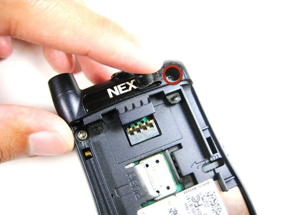 Lift up the right part of the Nextel logo and unscrew the screw underneath.
