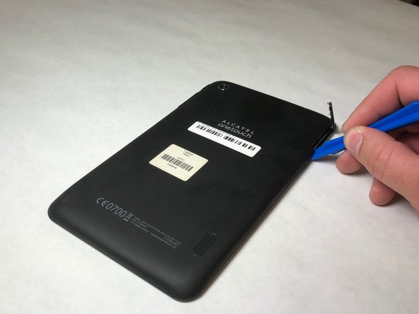 Use the plastic opening tool to pry around the edges of the back cover until it pops off.