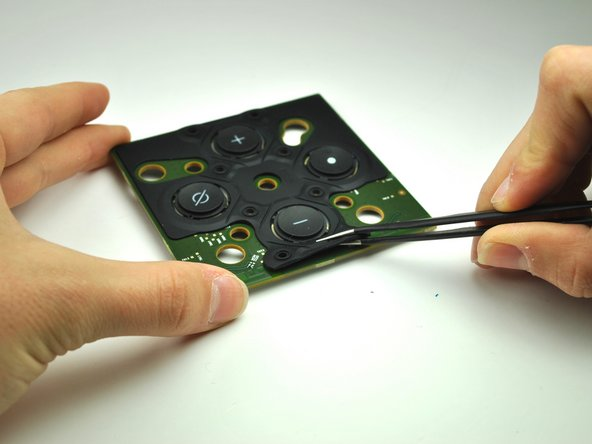Peel back the rubber button casing.