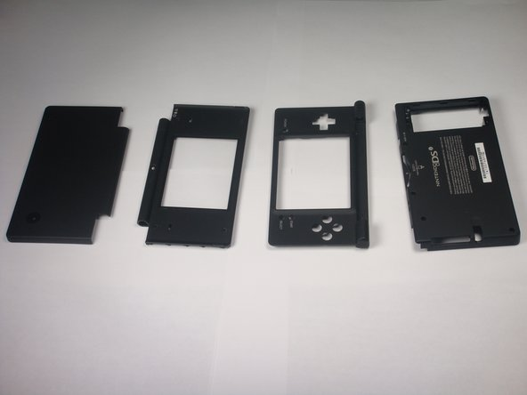 The complete DSi outer casing can now be replaced. Parts listed left to right: top cover, top LCD screen casing, touch LCD screen casing, and bottom cover.