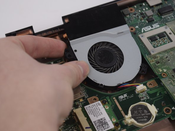 Image 3/3: Using the Spudger, carefully remove the white connector and lift the fan out of the casing.
