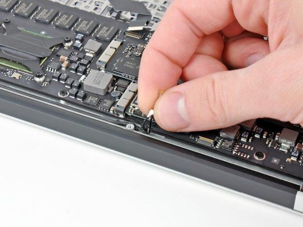 Fädle die Antennenkabel vorsichtig aus dem schlitzförmigen Einschnitt auf dem Logic Board.