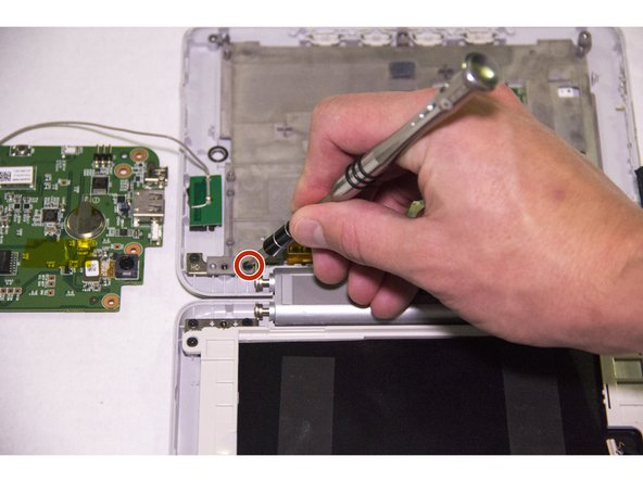 Using your J0 Phillips head screwdriver, remove the one 5 mm screw holding the gray plastic e-reader screen backing into place.