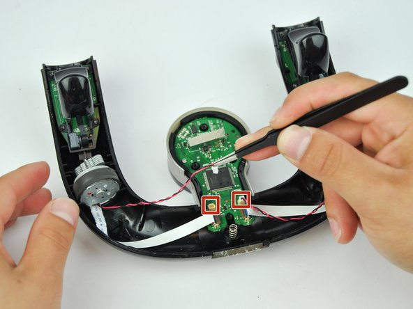 Use precision tweezers to remove the red and black wires that are attached to the circuit board.
