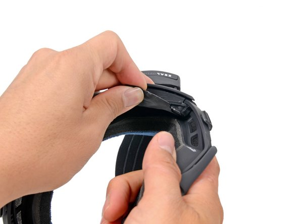 While firmly holding the battery cover, pull the bottom of the strap mount cover up and off of the frame