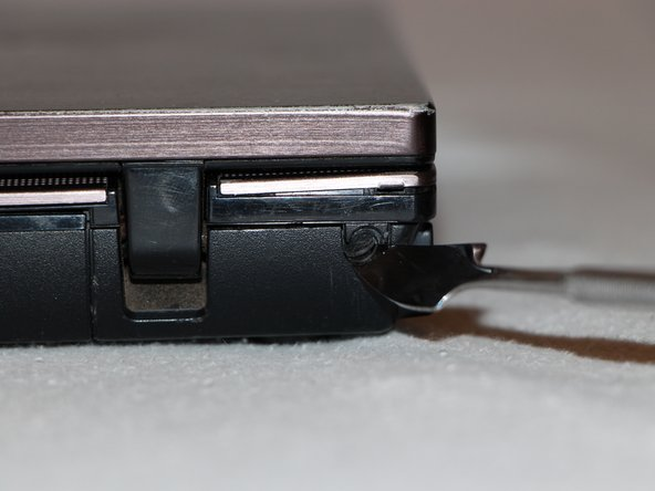 Use a metal spudger to peel off two rubber caps located on either side of the battery port.