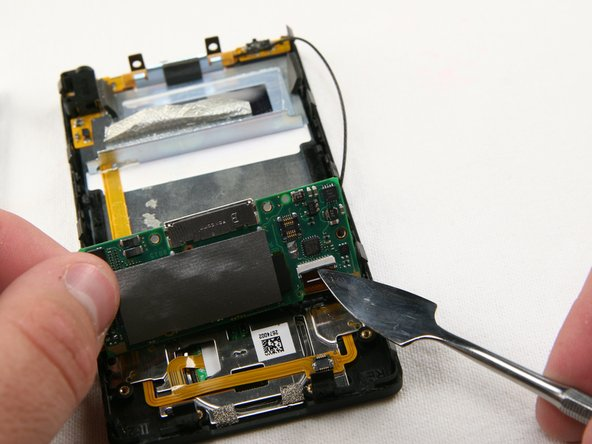 Carefully lift up the logic board located at the base of the Zune. Unclip the orange ribbon cable in the same manner as in the previous steps.