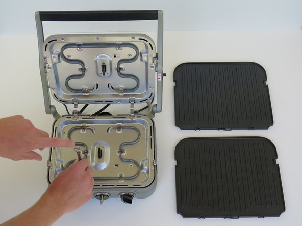 Remove cooking plates by pushing in the tabs on each side of the plate at the same time.