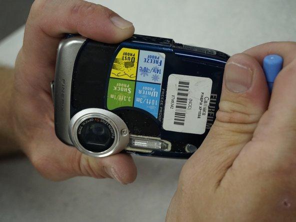 Carefully slide the case to the left. Avoid cracking the case on the lens.