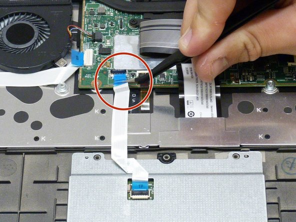 Using either fingernails or tweezers, lift the black cover on the ribbon cable and pull the cable loose from he motherboard.