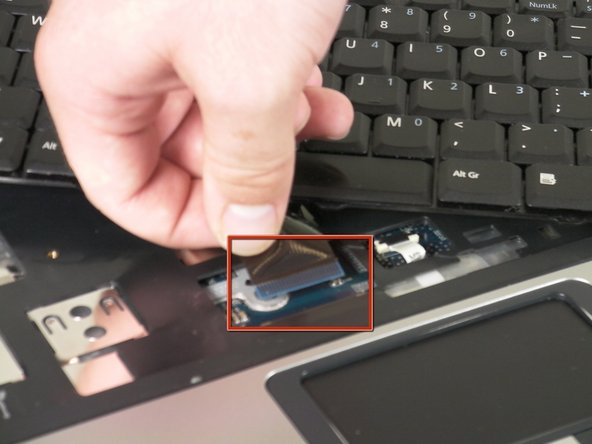 Release the catch on the ribbon socket, by sliding the two tabs toward the ribbon, then pull the ribbon, which is located under the keyboard, to detach it from the motherboard.