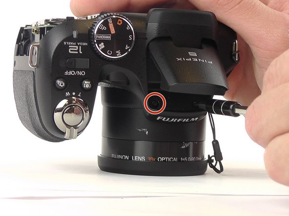Image 1/1: Using a J000 screwdriver, remove the two 4mm screws from the top of the camera.