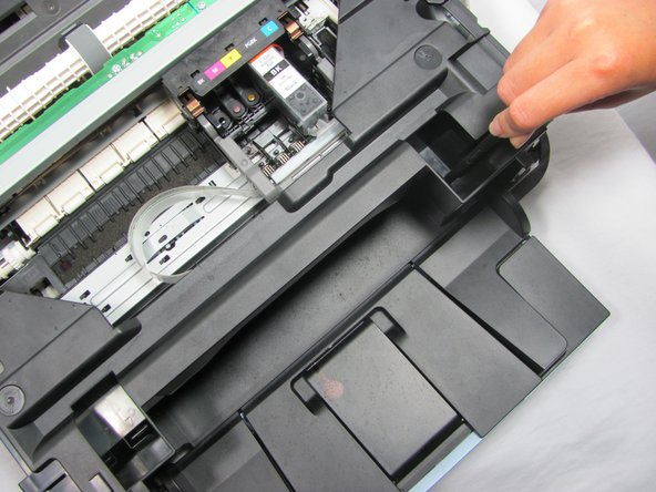Remove the plastic cover by depressing the clip located on the right side of the printer. Press the clip inwards until it clicks, and then lift the cover upwards and off the printer.