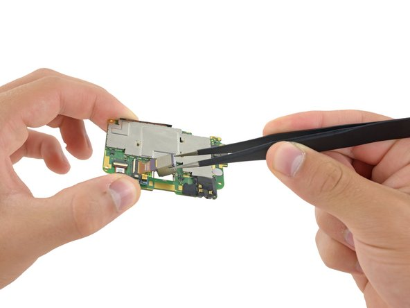 Use tweezers to lift and remove the rear camera from the logic board.