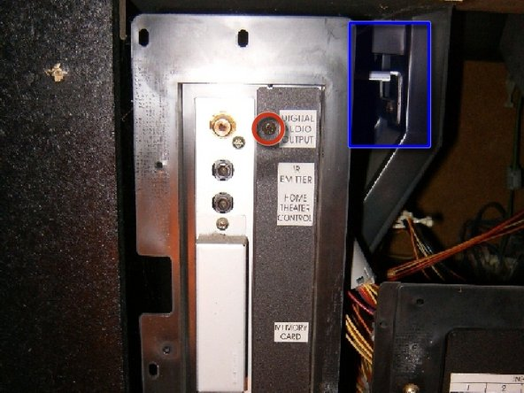 To the bottom right is a screw that connects a ground strap and holds the board to the chassis, undo that.