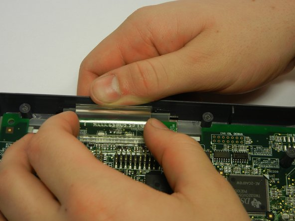 Pull the gray plastic casing away from the circuit board as you remove the clear, curved, plastic piece straight up.