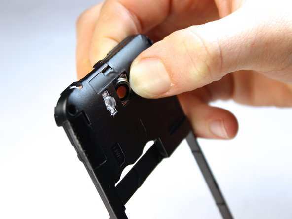 Use your finger to gently apply pressure against the lens until it pops out of the back of the midframe.