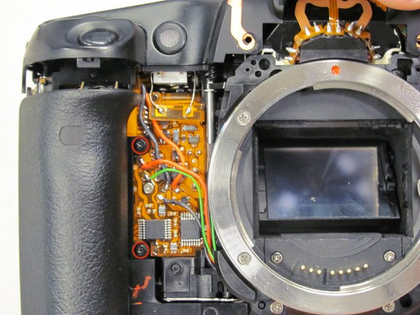 Remove two 5.5 mm screws from front of camera.