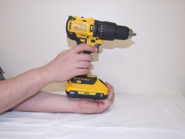 Compress the button on front side of the battery and move the drill and battery away from each other.