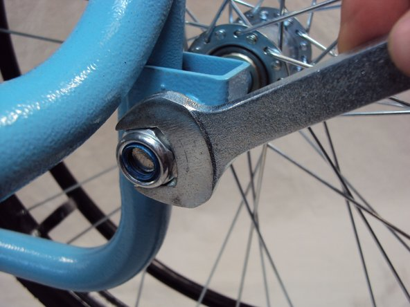 Image 2/2: '''Unscrew''' the bolt on the outside of the wheel by using a 19 mm socket wrench.
