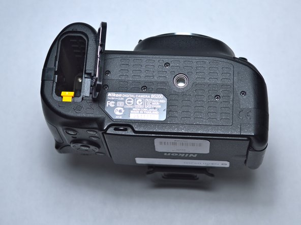 Press the yellow tab downwards to release the battery, and then hold the camera upright to allow the battery to slip out.