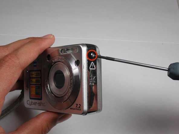 Remove the screw with a Phillips #00 Screwdriver from the right side of the camera (with '3x optical zoom' engraved on the side panel).