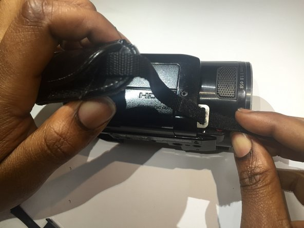 Turn the camcorder to the side and remove the strap.