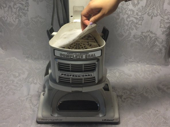 First unclip the dust canister from the body of the vacuum by lifting up the grey tabs on either side of the canister.