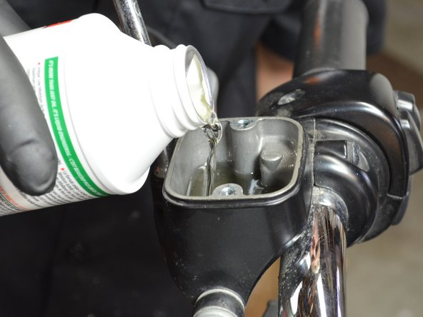 Image 2/3: Refill the master cylinder with fresh brake fluid until the level of fluid is even with the metal protrusion in the rear right corner of the master cylinder.