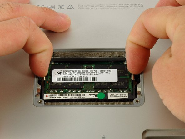 """Image 1/1: Release the tabs on each side of the RAM chip at the same time.  These tabs lock the chip in place and releasing them will cause the chip to """"pop"""" up."""