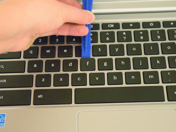 Using a plastic opening tool, place it beneath the key in question and pry it off.