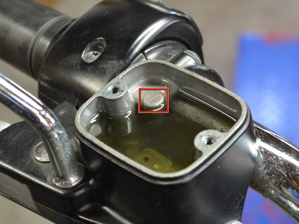 Refill the master cylinder with fresh brake fluid until the level of fluid is even with the metal protrusion in the rear right corner of the master cylinder.