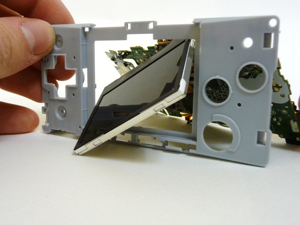 To remove the LCD screen, carefully angle it until it is diagonal to the square hole in the plastic guard and slide it out.