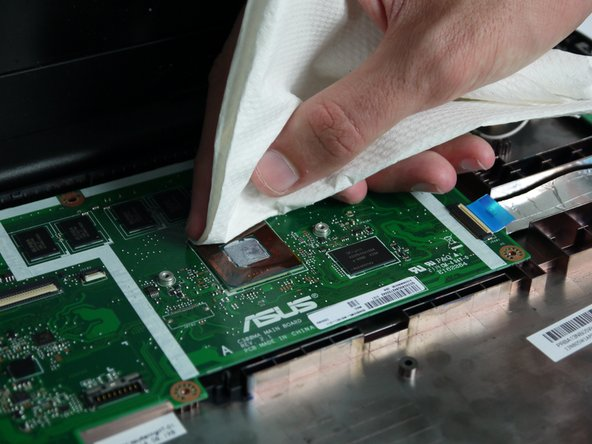 Using a paper towel, gently wipe off the existing thermal paste from both the CPU and the metal cover.