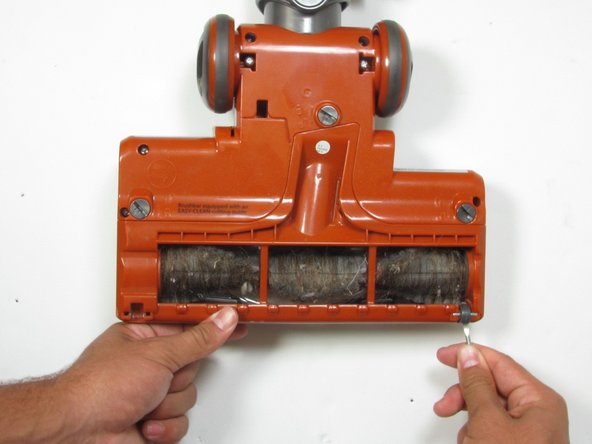 Locate and remove the two small wheels below the roller brush by prying with a plastic prying tool.