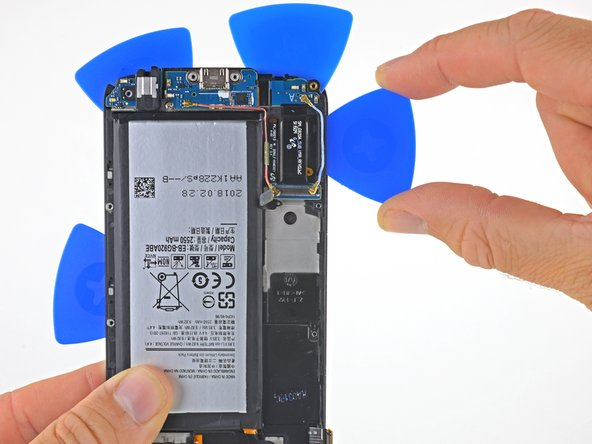 Slide an opening pick along the side of the phone opposite the battery to separate the adhesive underneath.