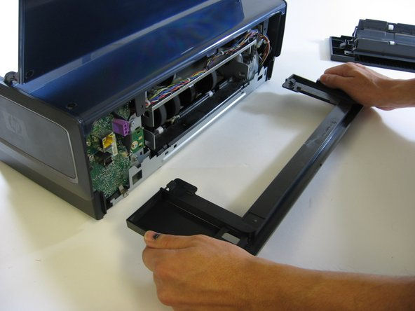 Next, you'll need to remove the rear support structure. Using your screwdriver, unscrew each screw and set them to the side. The entire back panel of your printer should now be exposed.