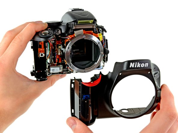 Firmly separate the front panel from the main camera body. You will feel some resistance since the chassis parts fit tightly together; this is to be expected.