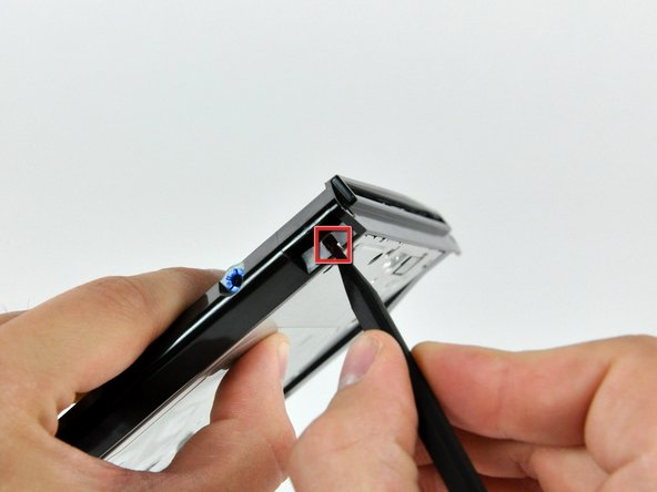 Using the tip of a spudger, press the optical drive bracket tab out of its slot on the side of the optical drive.