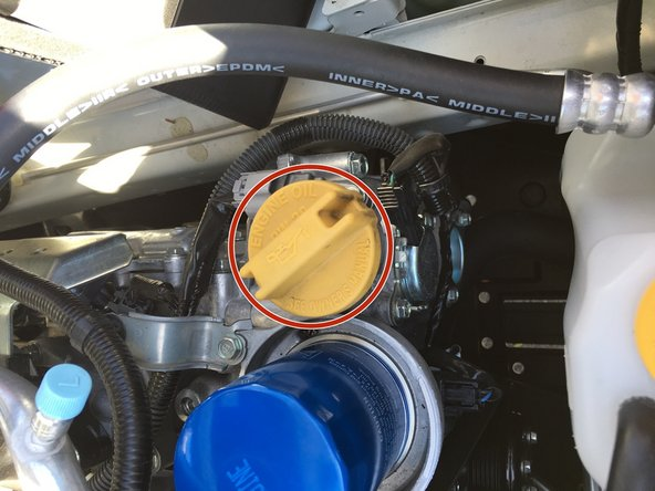 Unscrew cap for engine oil.  This is located directly to the left of the oil filter.