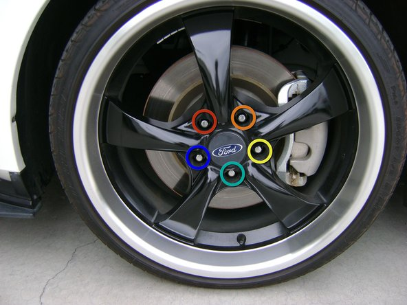 Place a new wheel on the hub, and then fix it in place by tightening the lug nuts clockwise. In other words, skip every other nut as you go around the wheel.