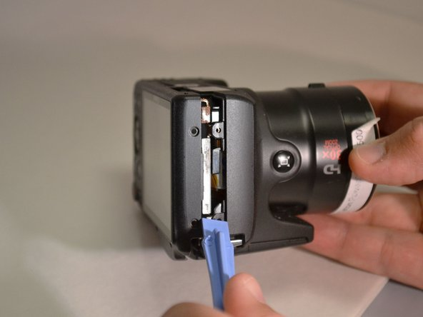 Using the plastic pry tool, remove the back cover from camera.