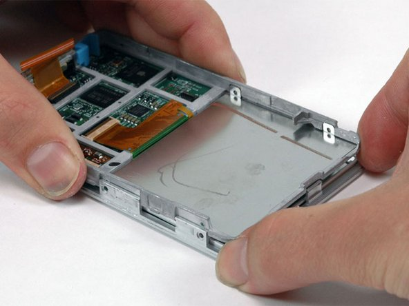 Image 1/1: Carefully work around the edges of the iPod to separate the front panel from the gray metal framework.