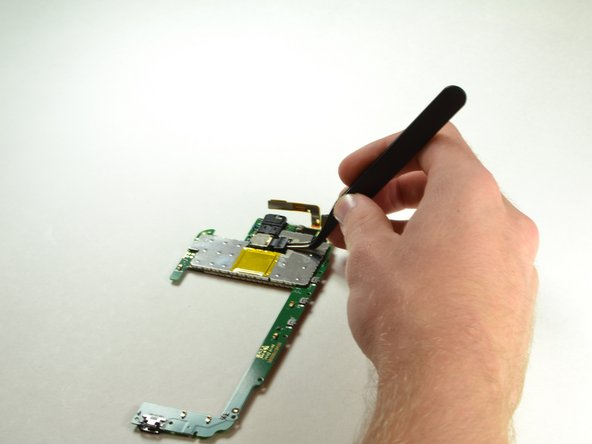 Use the prying tweezers to remove the rear facing camera connector on its right side.