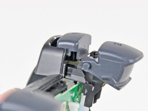 Image 1/2: The trigger button assembly is properly installed when the lip on the trigger button retainer sits flat against the motherboard.