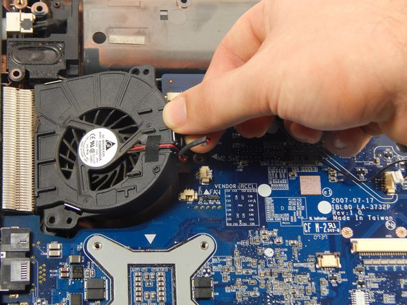 Using the opening tool, gently pry up and remove the fan.