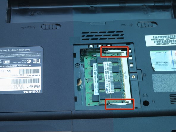 Use your fingernails to push the white and silver retaining clips away from each side of the RAM card.