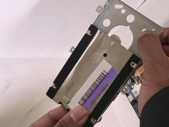Pull the hard drive out of the metal frame.